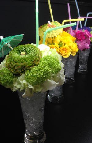 Летен коктейл от различни цветя в коктейлна чаша с чадърче и сламка.